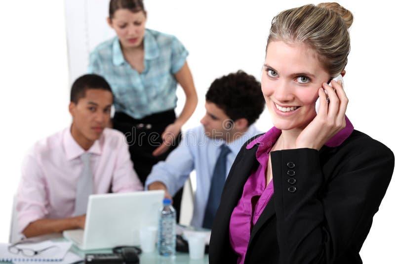 Lächelnde Frau, die einen Anruf entgegennimmt stockfotografie