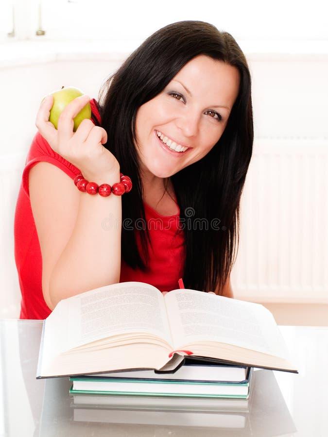 Lächelnde Frau, die einen Apfel und ein studyi anhält stockfotografie