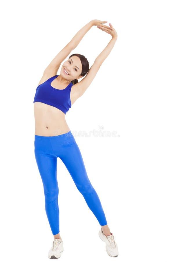 Lächelnde Frau, die für ein Training ausdehnt und aufwärmt stockfotos