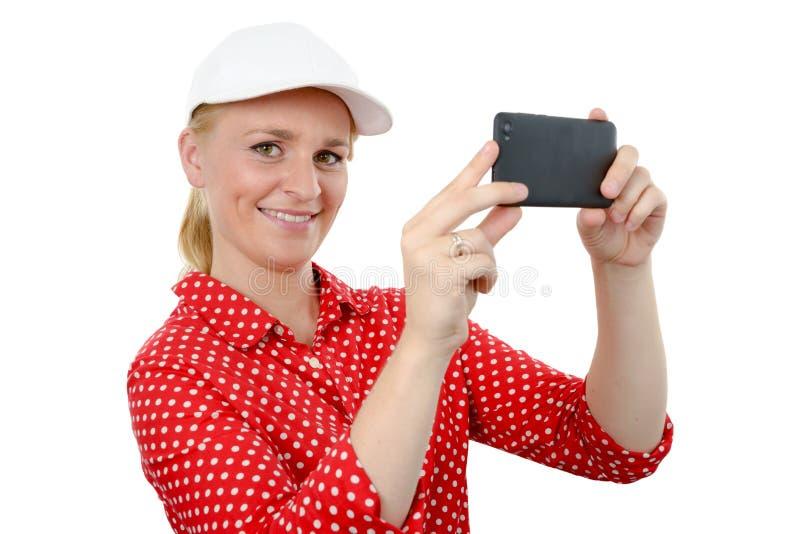 Lächelnde Frau, die Foto mit Smartphonekamera, auf Weiß macht lizenzfreie stockfotografie