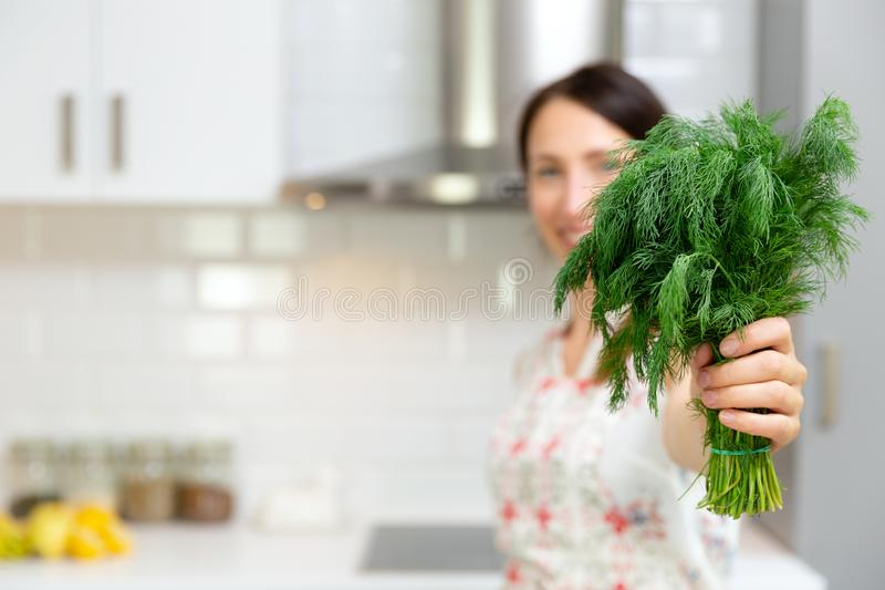 Lächelnde Frau, die frisches organisches Dillkraut hält Frau, die köstliche und gesunde Nahrung in der Hauptküche zubereitet lizenzfreie stockfotos