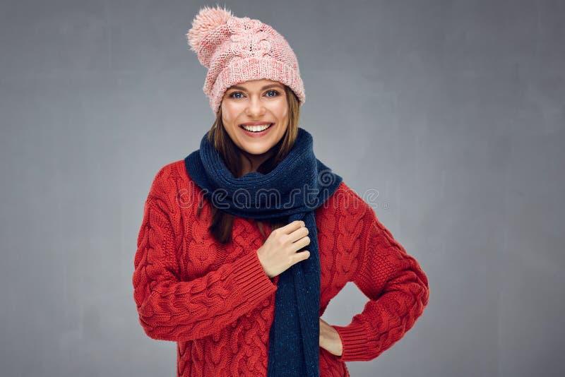 Lächelnde Frau, die gestrickte Strickjacke, Winterschal und Schale trägt stockfoto