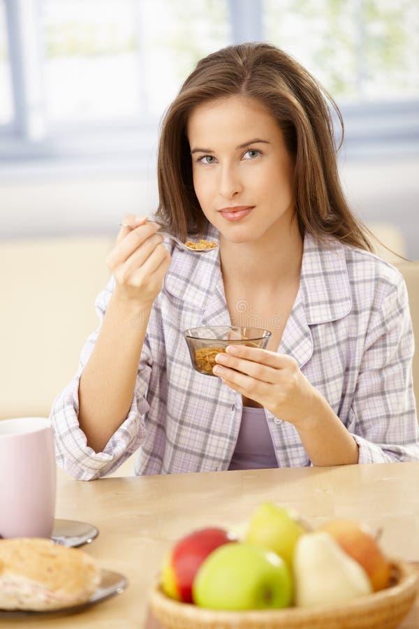 Lächelnde Frau, die Getreide isst lizenzfreie stockbilder