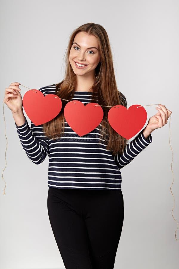 Lächelnde Frau, die Girlande von fünf roten Papierherzen hält lizenzfreie stockfotos