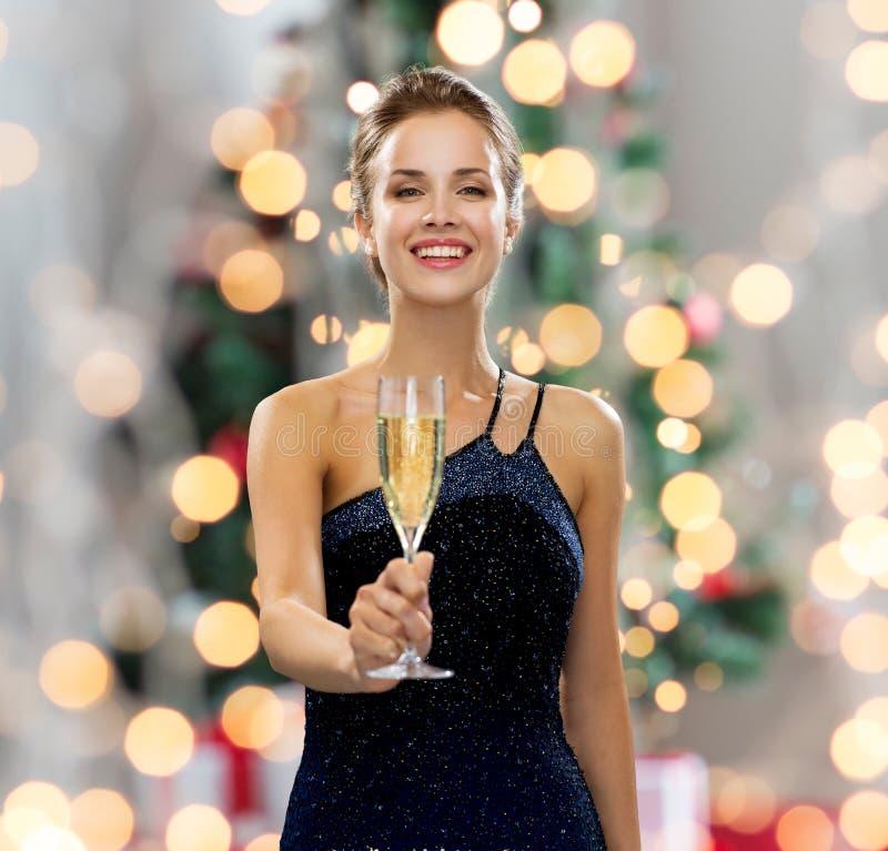 Lächelnde Frau, die Glas Sekt hält stockfotos