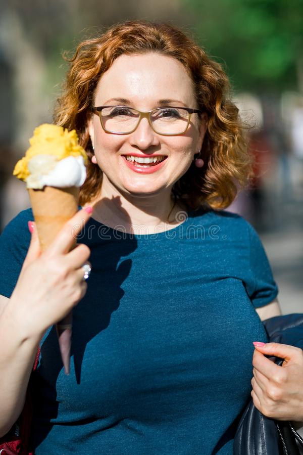 Lächelnde Frau, die große Eiscreme hat stockfoto