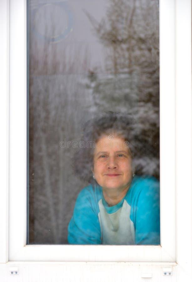Lächelnde Frau, die heraus Fenster schaut lizenzfreie stockfotos