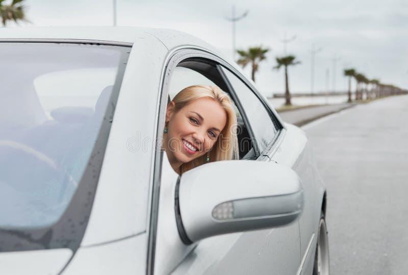 Lächelnde Frau, die heraus vom Autofenster schaut lizenzfreie stockfotos