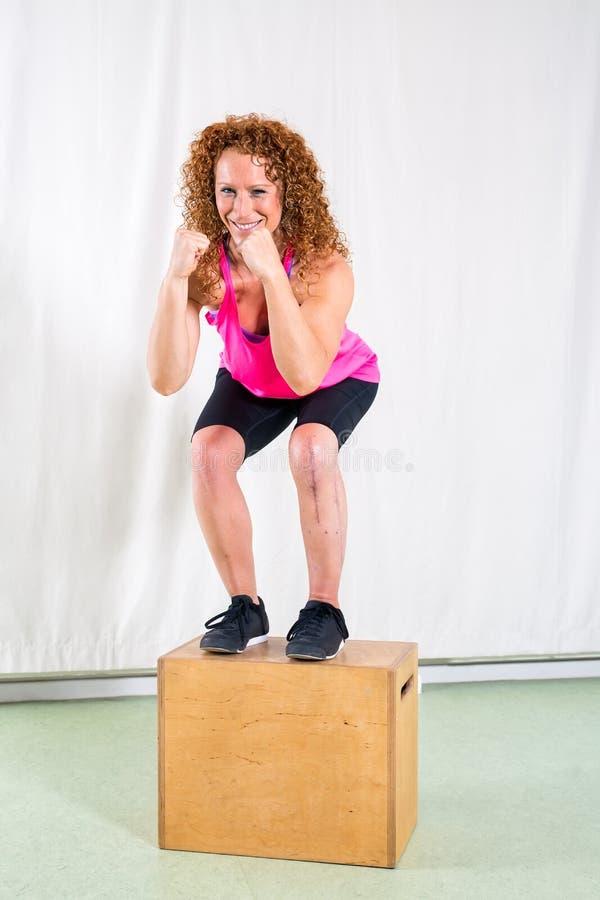 Lächelnde Frau, die Hocken auf Kasten durchführt lizenzfreie stockbilder