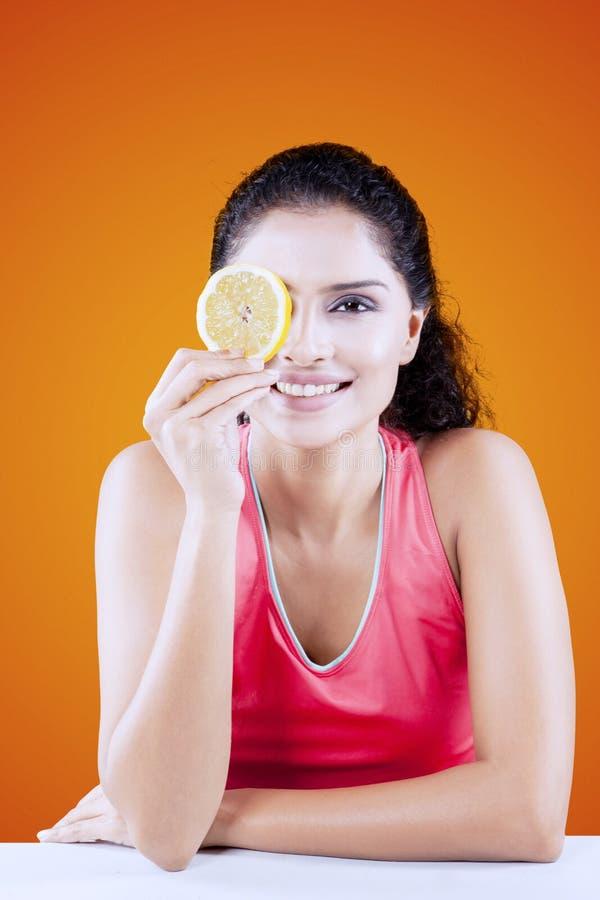 Lächelnde Frau, die ihr ein Auge mit Orange bedeckt lizenzfreie stockbilder
