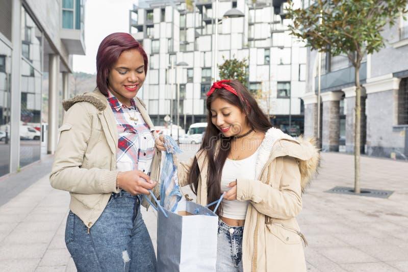 Lächelnde Frau, die ihr neue Kleidung zu ihrem Freund im stree zeigt stockfotos