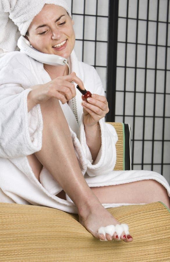 Lächelnde Frau, die ihre Nägel malt stockfotos