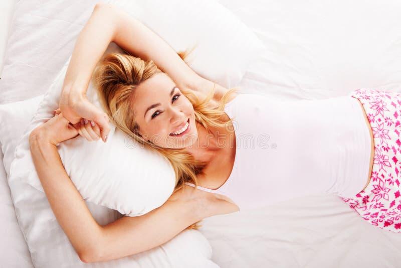 Lächelnde Frau, die in ihrem Bett liegt lizenzfreies stockbild