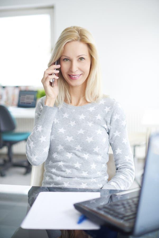 Lächelnde Frau, die ihren Handy verwendet lizenzfreie stockfotos