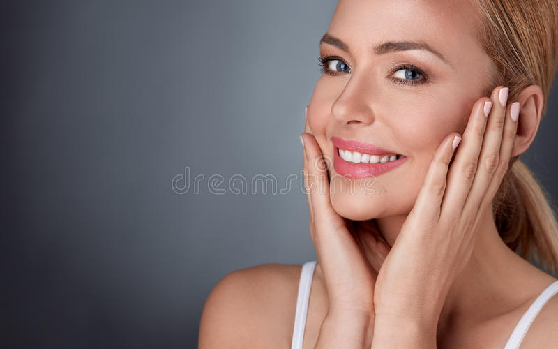 Lächelnde Frau, die in ihrer gesunden Haut genießt lizenzfreie stockfotos