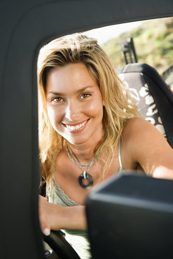 Lächelnde Frau, die im Auto sitzt lizenzfreies stockbild