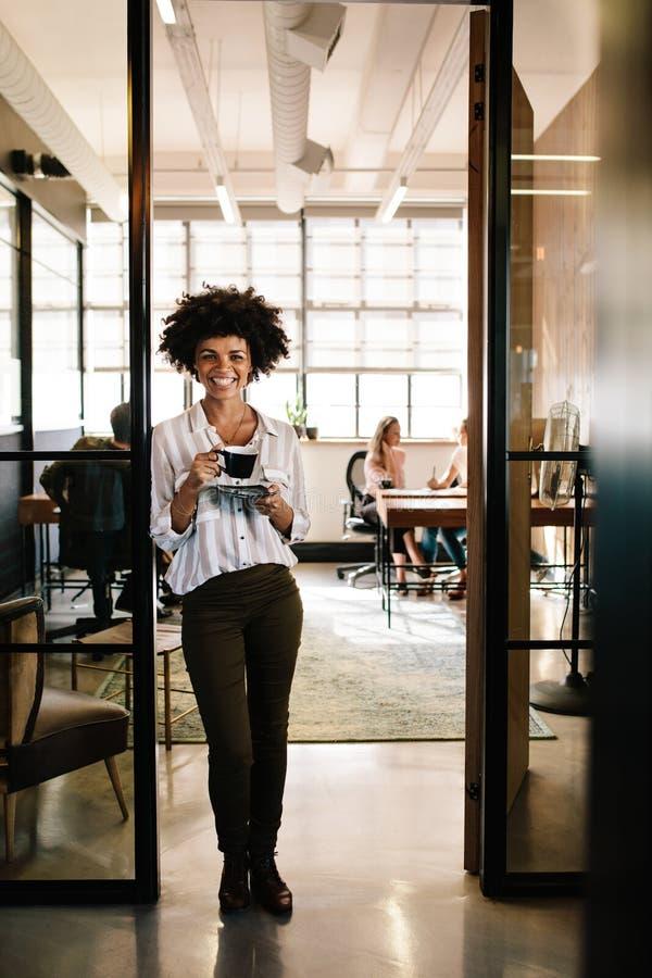 Lächelnde Frau, die im Büroeingang mit Kaffee steht stockfoto