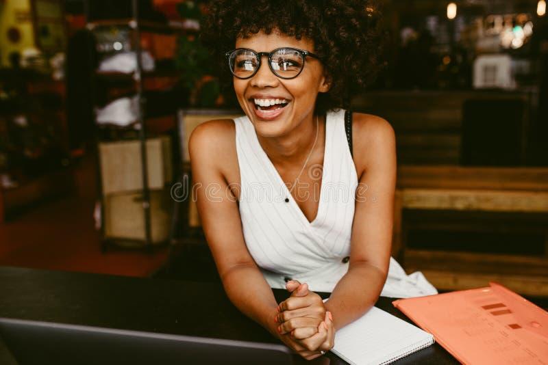 Lächelnde Frau, die im Café sitzt stockfotografie