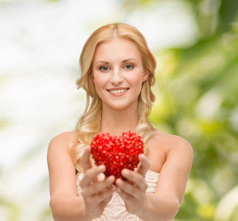 Lächelnde Frau, die kleines rotes Herz gibt stockfoto