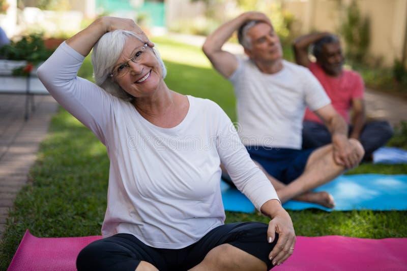 Lächelnde Frau, die Kopf beim Trainieren mit Freunden ausdehnt lizenzfreies stockfoto