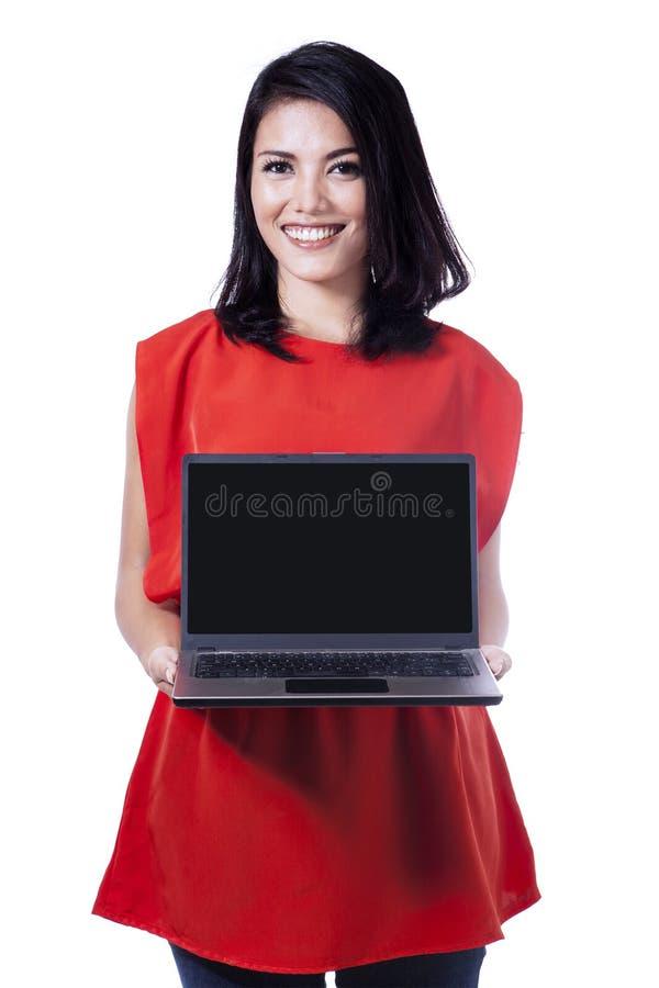Lächelnde Frau, die Laptopschirm zeigt stockfotografie