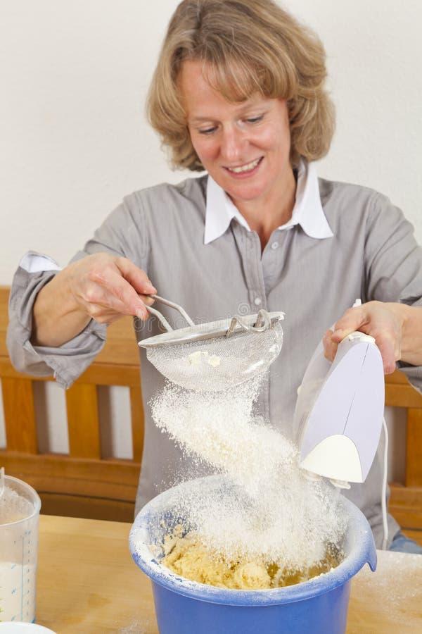 Lächelnde Frau, die Mehl in Teig siebt lizenzfreie stockfotos