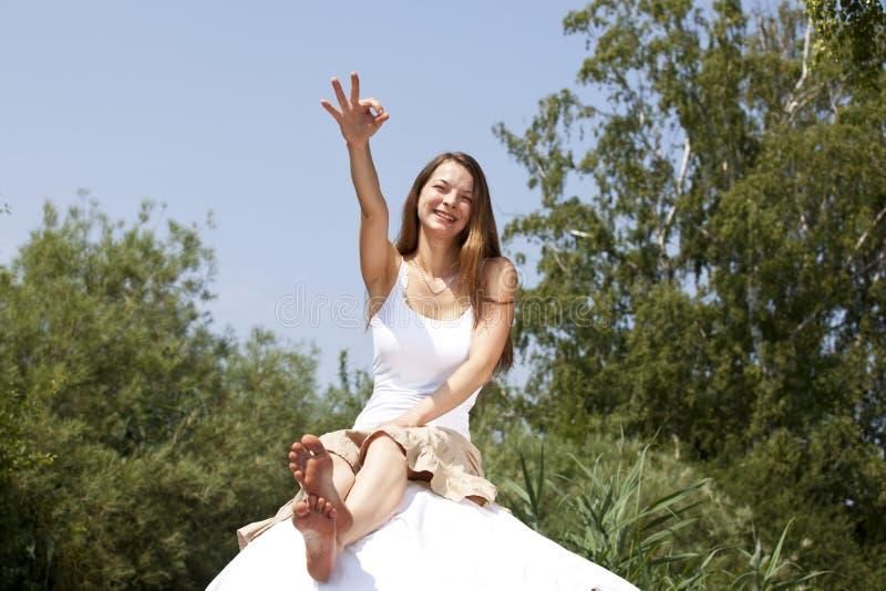 Lächelnde Frau, die mit dem okayzeichen aufwirft lizenzfreies stockbild