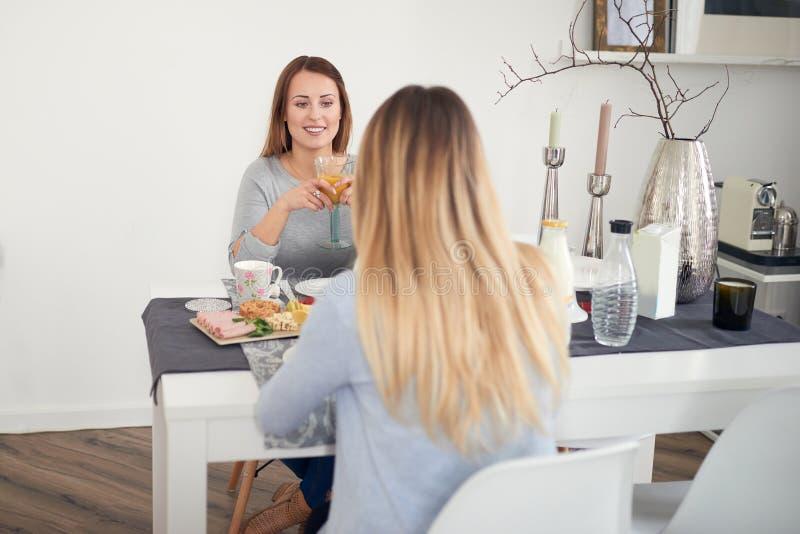 Lächelnde Frau, die mit ihrer Tochter frühstückt lizenzfreie stockfotografie