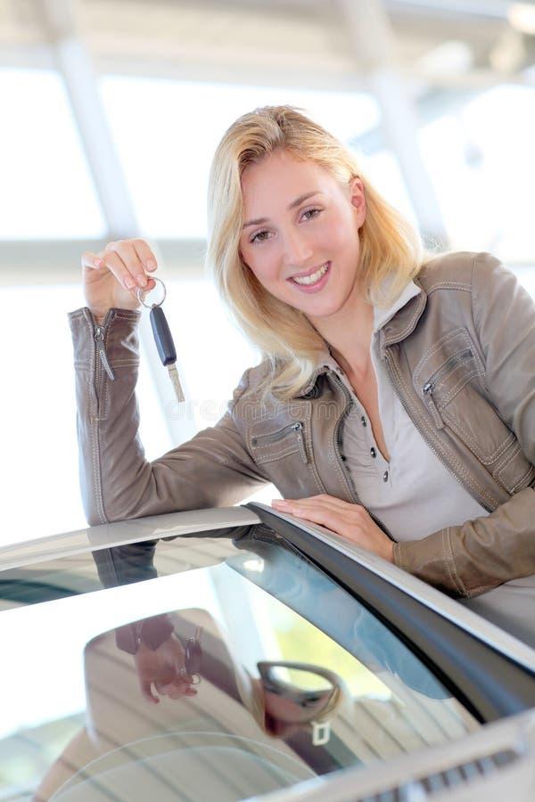 Lächelnde Frau, die neues Auto kauft stockfotos