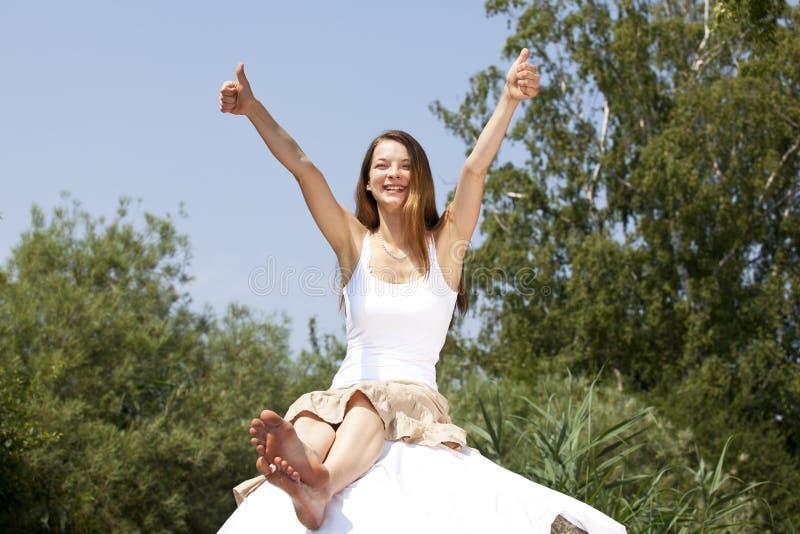 Lächelnde Frau, die oben beide Daumen aufwirft stockfoto