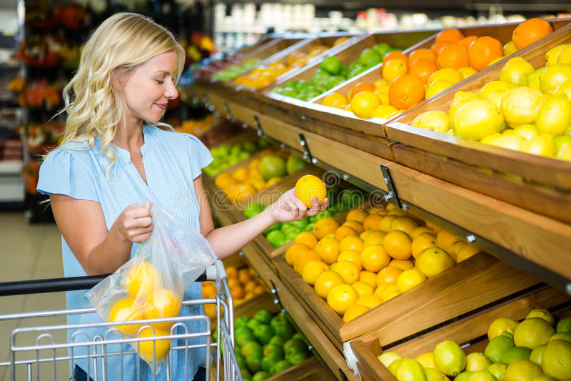 Lächelnde Frau, die Orangen in Plastiktasche einsetzt stockfotografie