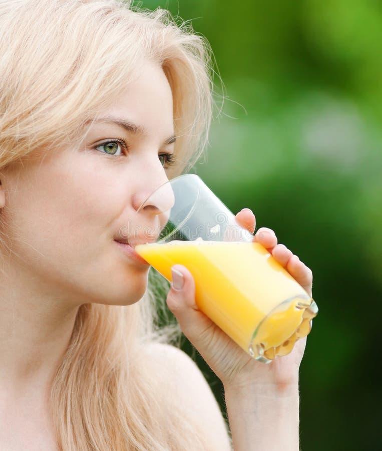 Lächelnde Frau, die Orangensaft trinkt lizenzfreie stockfotografie