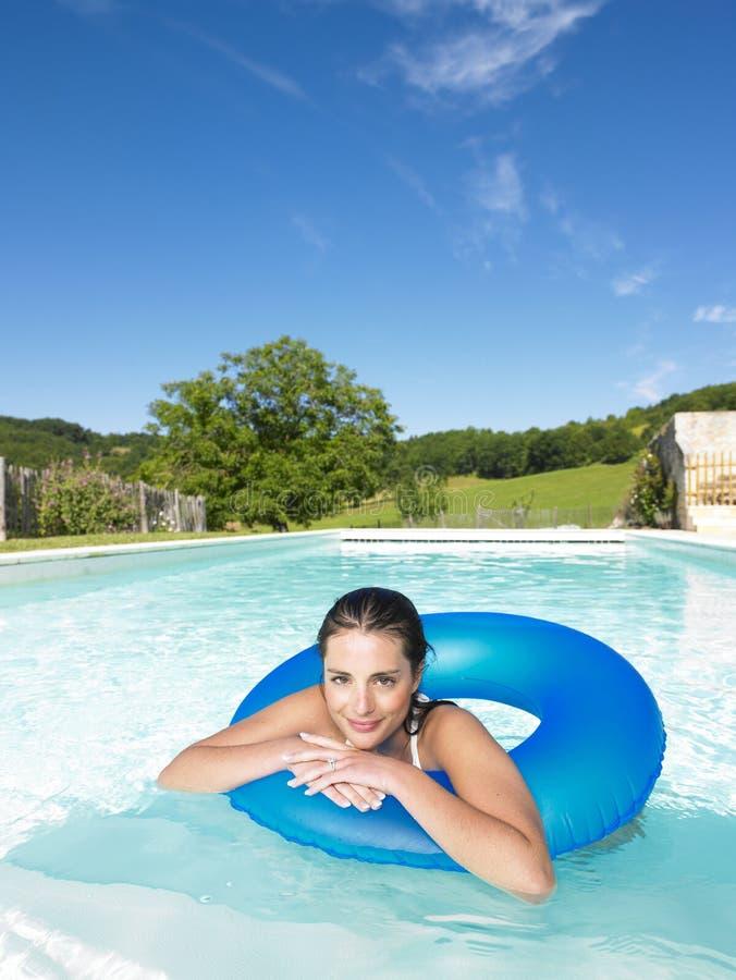 Lächelnde Frau, die in Pool schwimmt stockbild