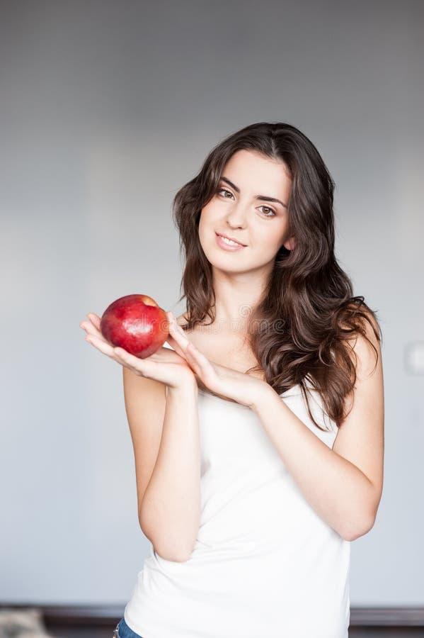 Lächelnde Frau, die roten Apfel hält Studio getrenntes Portrait stockfoto