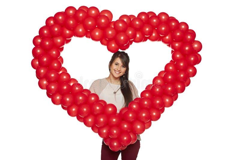 Lächelnde Frau, die rotes Ballonherz hält stockfotografie