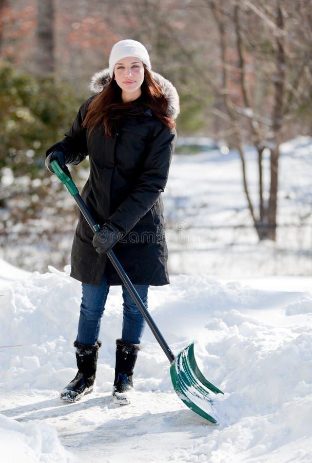 Lächelnde Frau, die Schnee schaufelt stockfoto