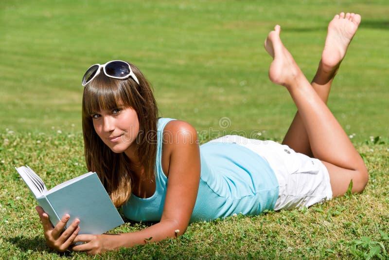 Lächelnde Frau, die sich auf Gras mit Buch hinlegt stockbilder