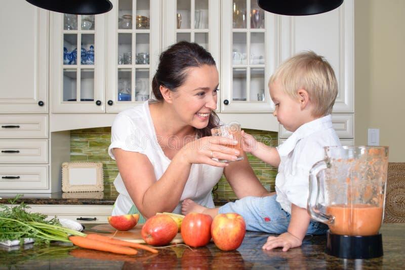 Lächelnde Frau, die Smoothie für kleinen Jungen macht lizenzfreies stockbild