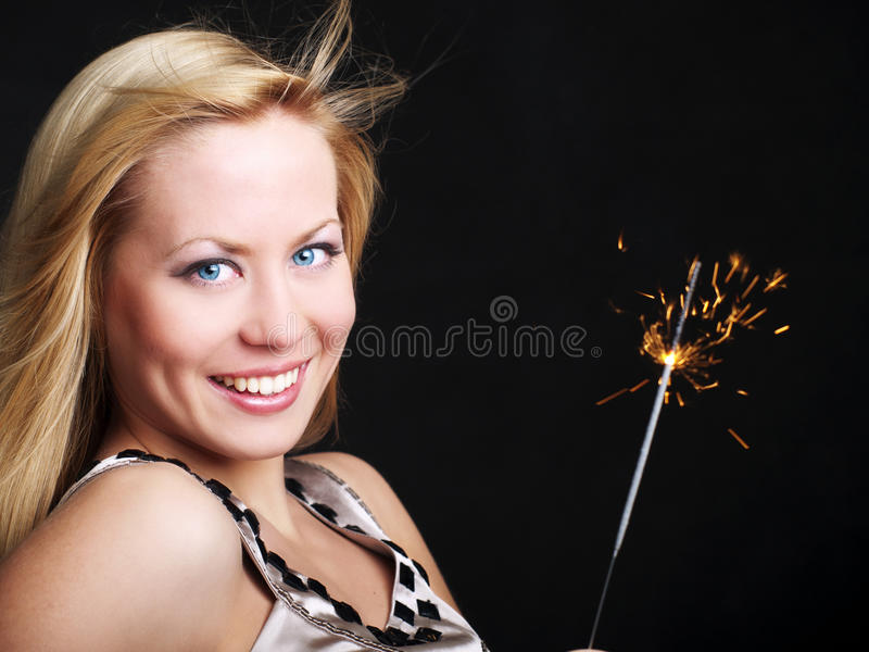 Lächelnde Frau, die Sparkler des neuen Jahres anhält stockfotos