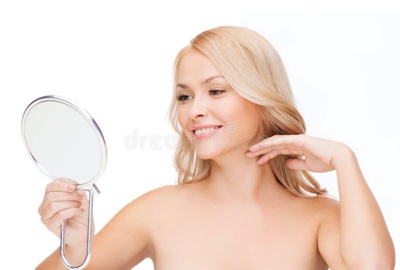 Lächelnde Frau, die Spiegel betrachtet stockfotos