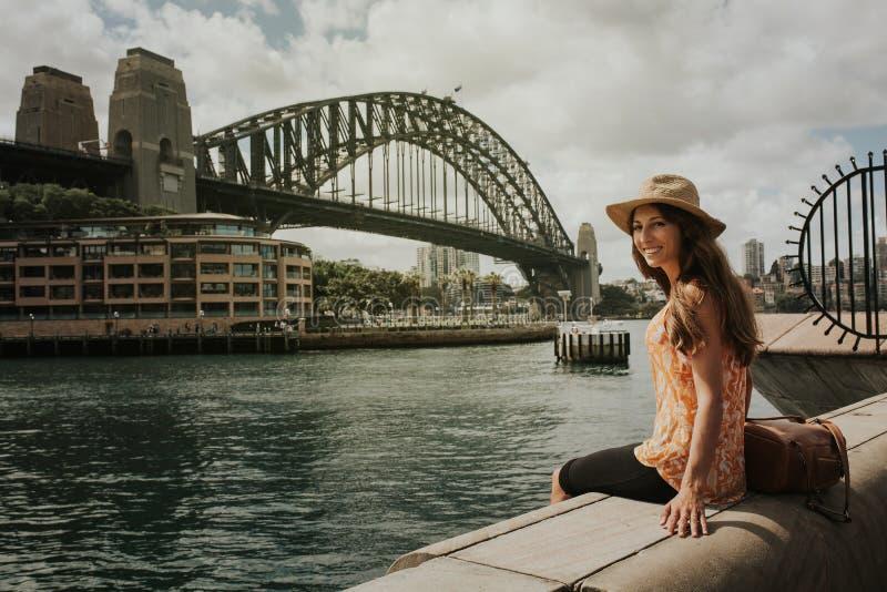 Lächelnde Frau, die in Sydney vor Hafen-Brücke sitzt lizenzfreie stockfotografie