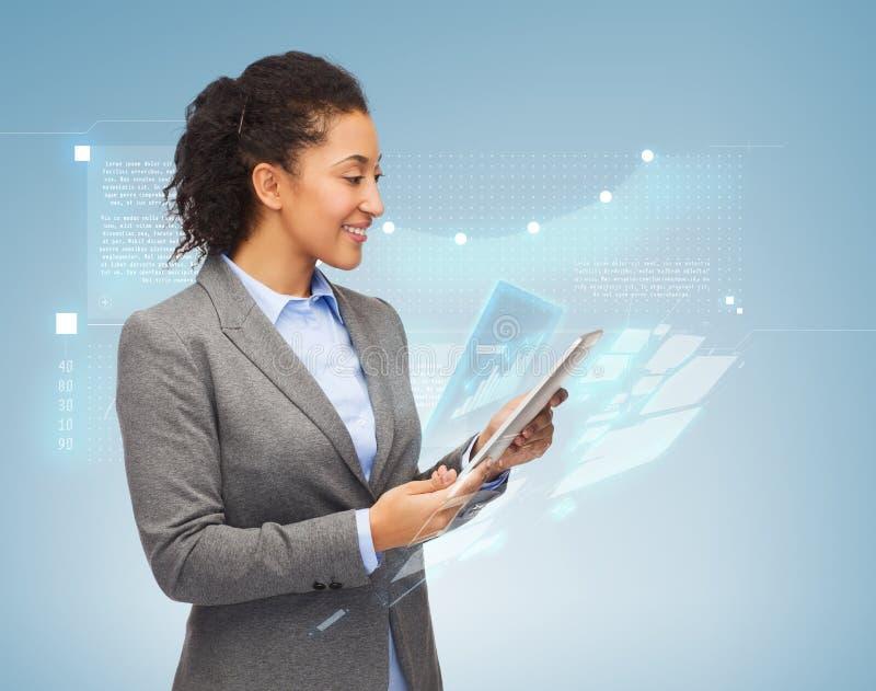 Lächelnde Frau, die Tabletten-PC betrachtet stockfotos