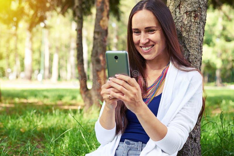 Lächelnde Frau, die unter Baum und der Anwendung des intelligenten Telefons sitzt stockbilder