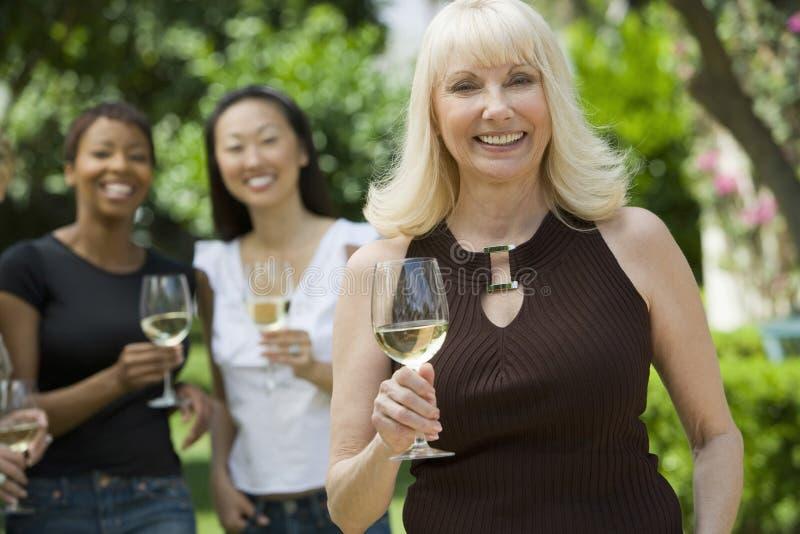 Lächelnde Frau, die Weinglas mit Freunden im Hintergrund hält stockfotografie