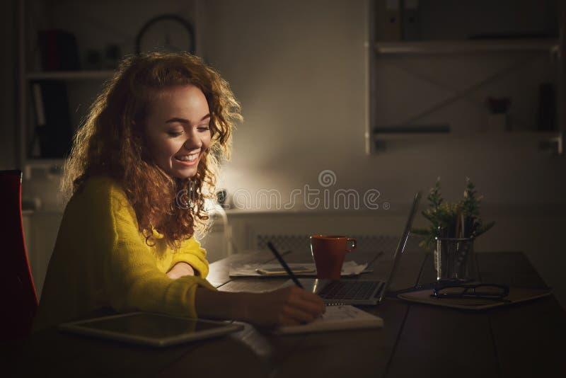 Lächelnde Frau, die zu Hause Anmerkungen am Abend macht lizenzfreies stockfoto