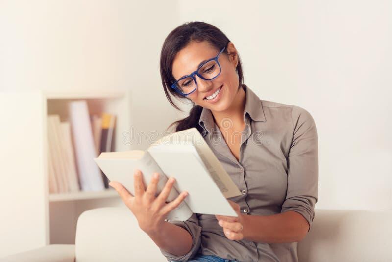 Lächelnde Frau, die zu Hause ein Buch auf Couch liest stockfotografie