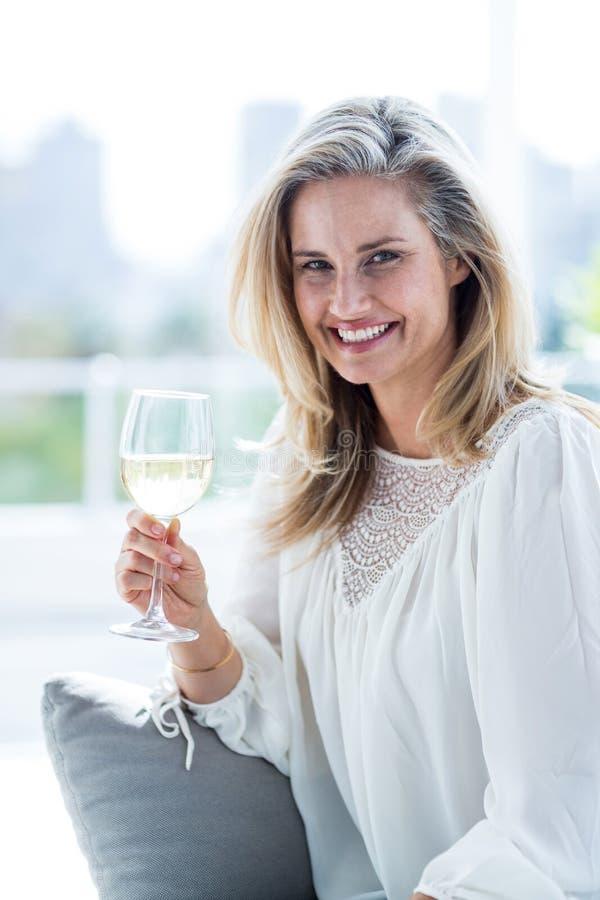 Lächelnde Frau, die zu Hause Weinglas hält lizenzfreie stockfotos
