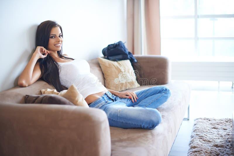 Lächelnde Frau, die zur Couch sitzt und sich lehnt lizenzfreies stockfoto