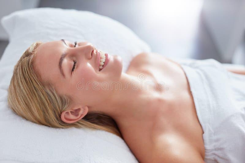 Lächelnde Frau in einem Tagesbadekurort, der auf Massagetabelle sich entspannt lizenzfreie stockfotografie