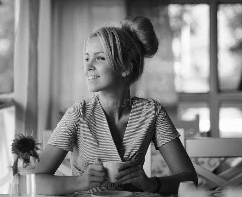 Lächelnde Frau in einer guten Laune mit Tasse Kaffee stockbilder